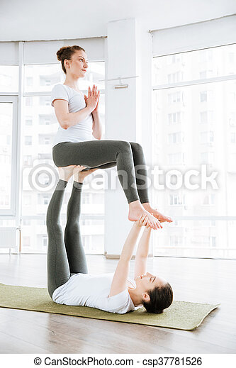 two young women doing acro yoga exercises in studio together. Black Bedroom Furniture Sets. Home Design Ideas