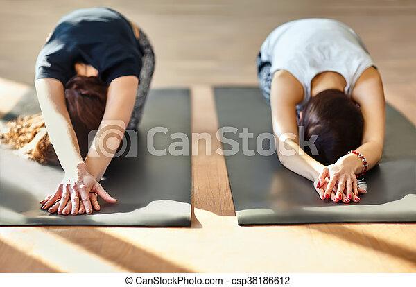 two young women doing yoga asana child's pose utthita