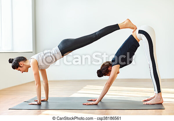 two young women doing yoga asana double downward dog adho