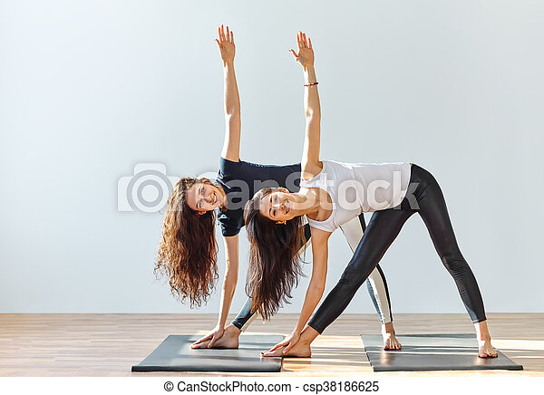 Two young women doing yoga asana extended triangle pose - csp38186625