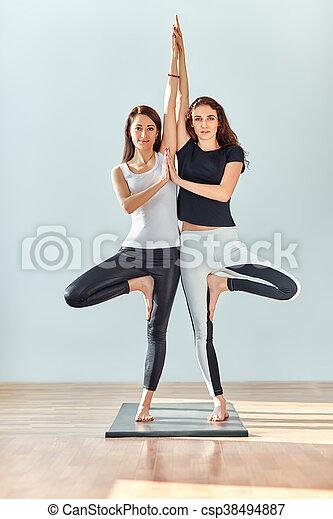 two young women doing yoga asana tree pose vrikshasana