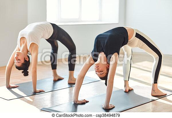 two young women doing yoga asana upward bow wheel pose