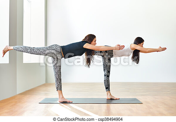 two young women doing yoga asana warrior iii pose