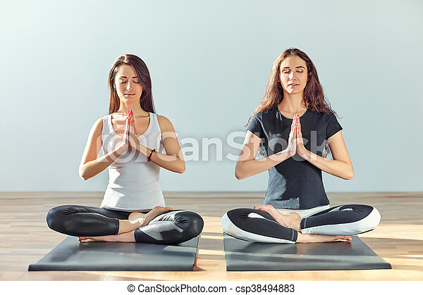 two young women meditating in lotus pose with hands in
