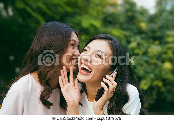 Two young women socializing outdoors. - csp61079579