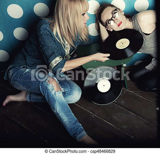 Two young women with vinyl records in his hands - csp48466829