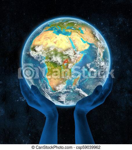 Uganda on planet Earth in hands - csp59039962