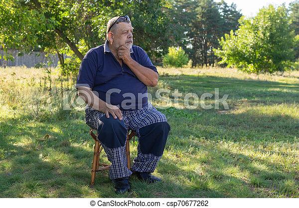 Ukrainian thoughtful senior man sitting on a stool in summer garden - csp70677262