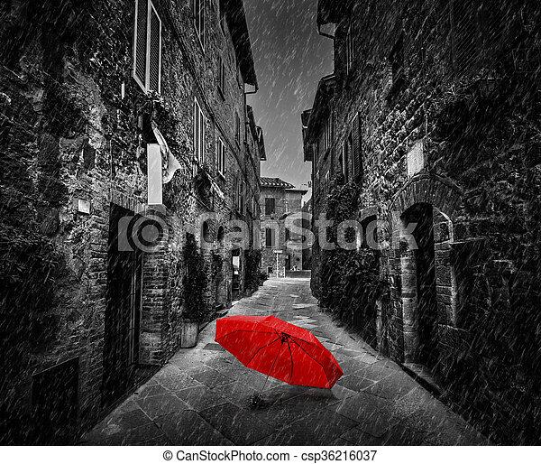 Umbrella on dark street in an old Italian town in Tuscany, Italy. Raining. - csp36216037