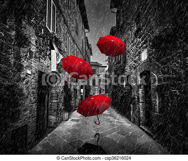 Umrbellas flying with wind and rain on dark street in an old Italian town in Tuscany, Italy - csp36216024