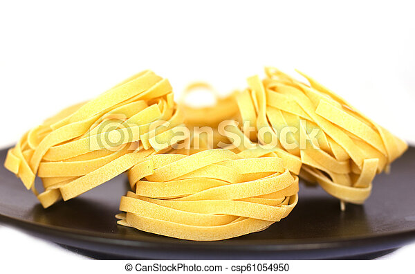Uncooked tagliatelle on a black ceramic plate. Isolated - csp61054950