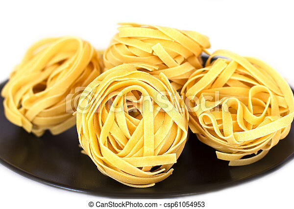 Uncooked tagliatelle on a black ceramic plate. Isolated - csp61054953