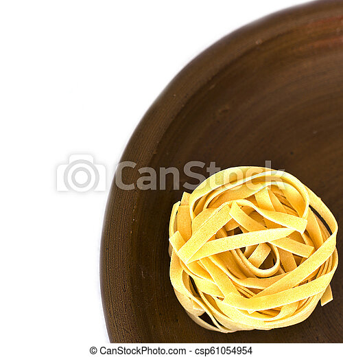 Uncooked tagliatelle on a ceramic plate. Isolated - csp61054954