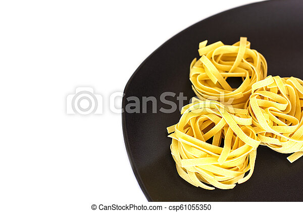 Uncooked tagliatelle on a ceramic plate. Isolated - csp61055350