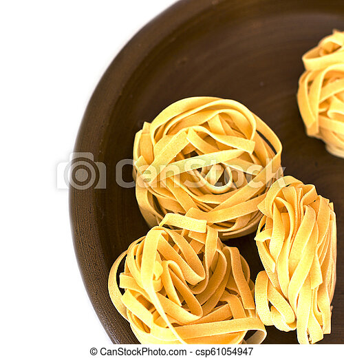 Uncooked tagliatelle on a ceramic plate. Isolated - csp61054947