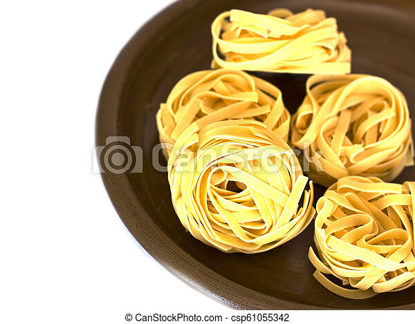Uncooked tagliatelle on a ceramic plate. Isolated - csp61055342