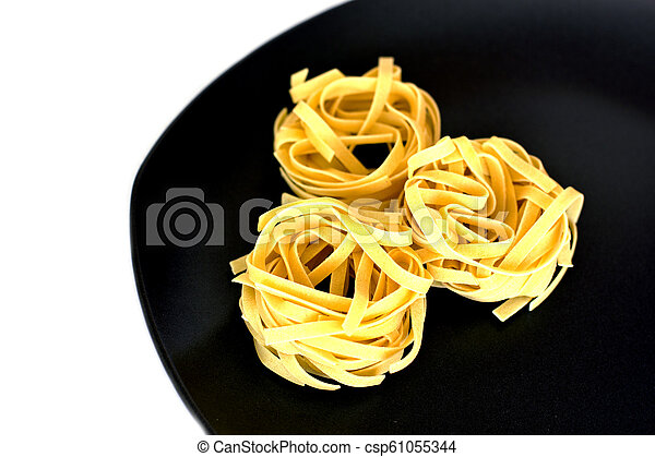 Uncooked tagliatelle on a ceramic plate. Isolated - csp61055344