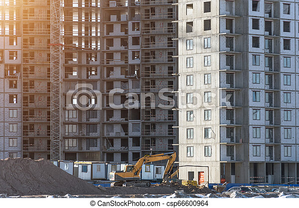 Under construction apartment building and residential real estate, excavator on the ground - csp66600964