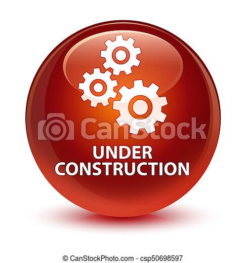 Under construction (gears icon) glassy brown round button - csp50698597