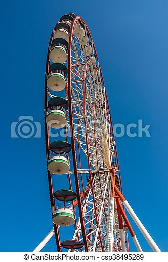 Underside view of a ferris wheel on sky background - csp38495289