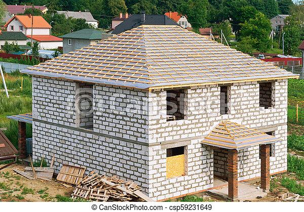 Unvollendetes Haus aus weißem Ziegelstein, Bau des Daches des Hauses - csp59231649
