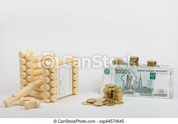 Unfinished toy house, next are Russian rubles banknotes and coins - csp44570645