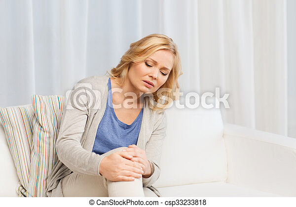 unhappy woman suffering from pain in leg at home - csp33233818