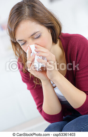 unhappy woman with paper napkin blowing nose - csp53361403