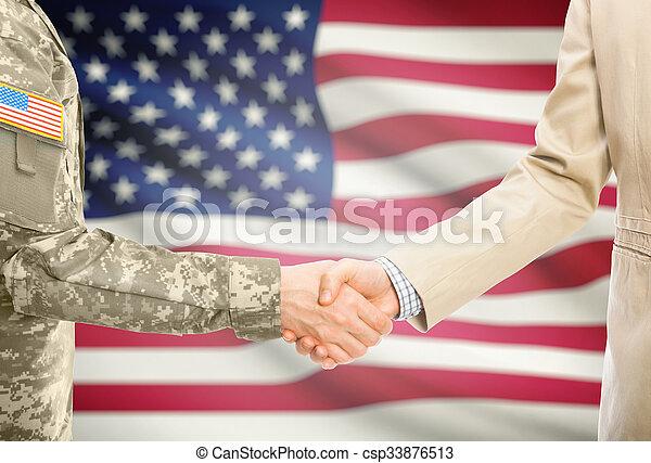 Un militar de EE.UU. en uniforme y un hombre civil en traje estrechando la mano con bandera nacional en el fondo - Estados Unidos - csp33876513