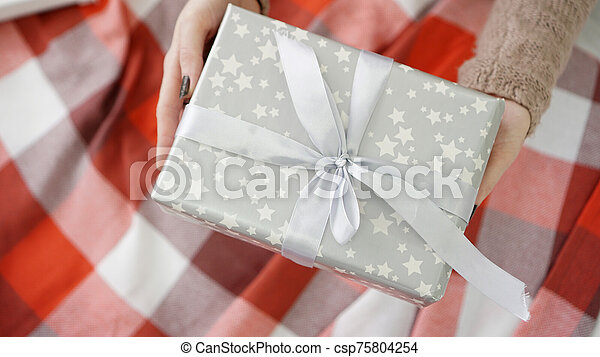 Unpacking Christmas presents. Woman holds and opening presents on warm plaid - csp75804254