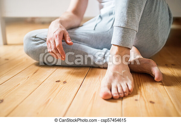 Unrecognizable man sitting on the floor in bedroom at home. - csp57454615