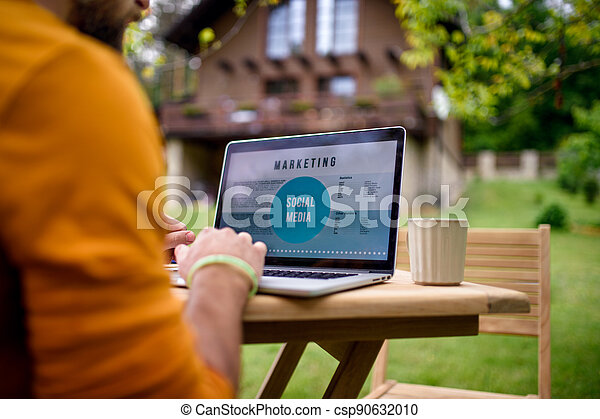 Unrecognizable man with laptop working outdoors in garden, home office concept. - csp90632010