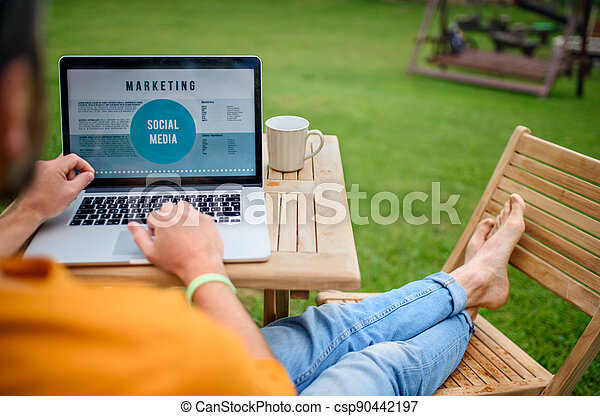 Unrecognizable man with laptop working outdoors in garden, home office concept. - csp90442197