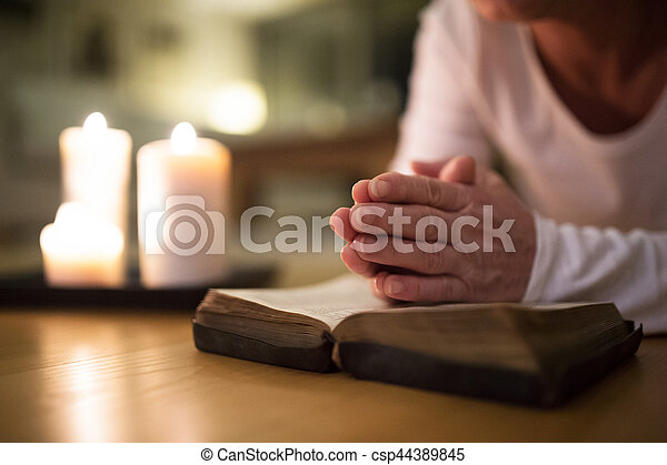 Unrecognizable senior woman praying, hands clasped together on h - csp44389845