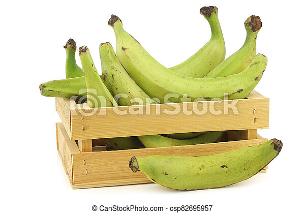 unripe baking bananas (plantain bananas) in a wooden crate - csp82695957