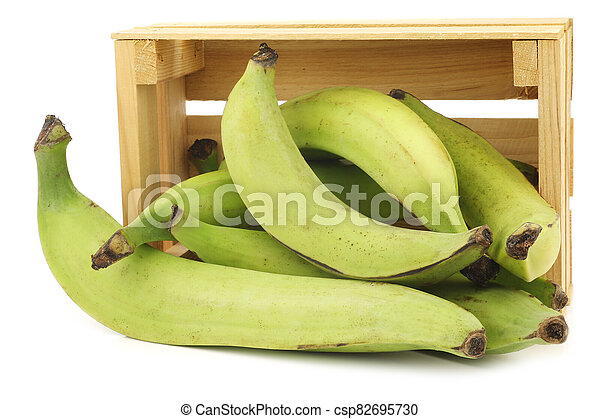 unripe baking bananas (plantain bananas) in a wooden crate - csp82695730