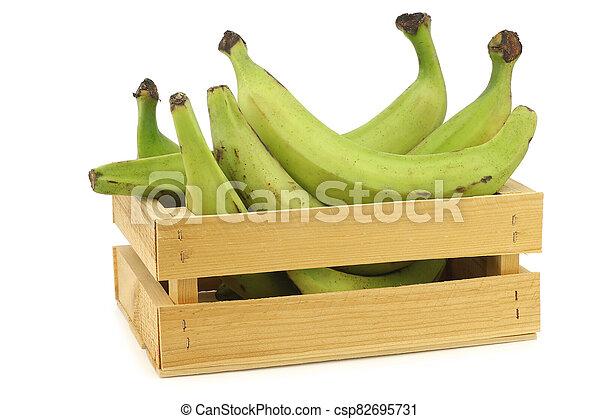 unripe baking bananas (plantain bananas) in a wooden crate - csp82695731