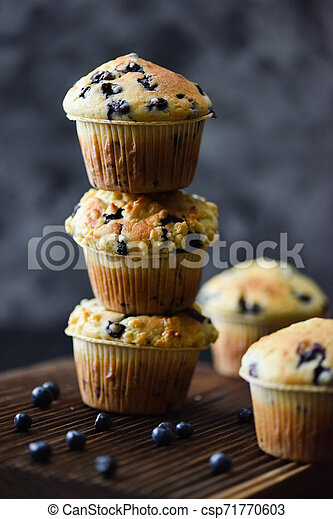 Unstable pile of freshly baked blueberry muffins on oak cutting board on dark background. Low key still life with natural lighting side view - csp71770603