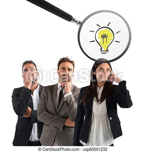 Glasvergrößerung untersucht die Idee einer jungen Geschäftsfrau - csp65501232