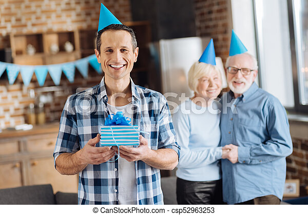 Upbeat Young Man Holding His Birthday Present