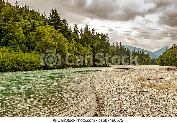 Upper Kitimat River, glacial green river, on a cloudy summer day. - csp87490572