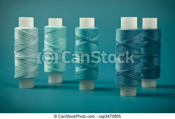 Upright colored spools of thread on a blue background - csp3470805