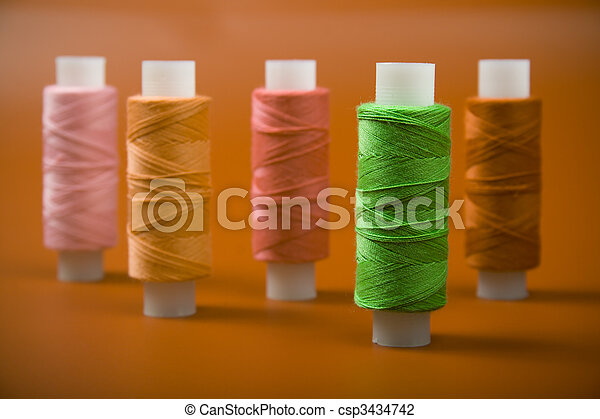 Upright colored spools of thread on a red background - csp3434742