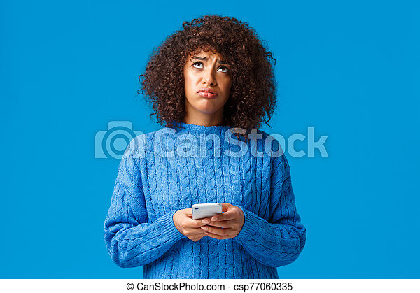 Upset and uneasy african-american gloomy girl feeling like loser, looking up at sky asking god why, sighing sad, holding smartphone, standing troubled and sulking over blue background - csp77060335