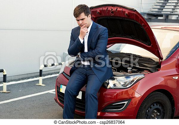 upset businessman sitting on bonnet of broken car - csp26837064