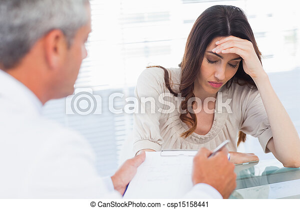 Upset woman listening to her doctor talking about a illness - csp15158441