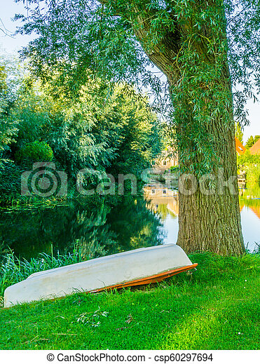 upside down boat in the park next to a tree with beautiful pond water landscape - csp60297694