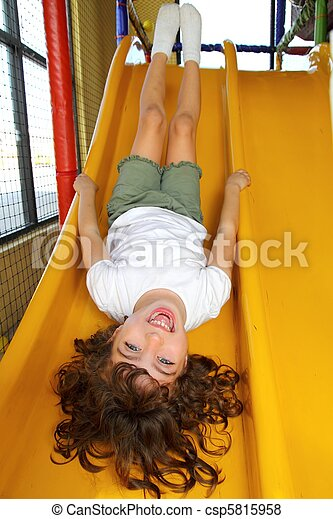 upside down little girl on playground slide laughing - csp5815958