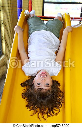 upside down little girl on playground slide laughing - csp5745290