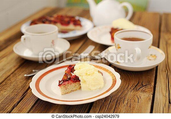Upside down plum pie with ice-cream and black tea - csp24042979